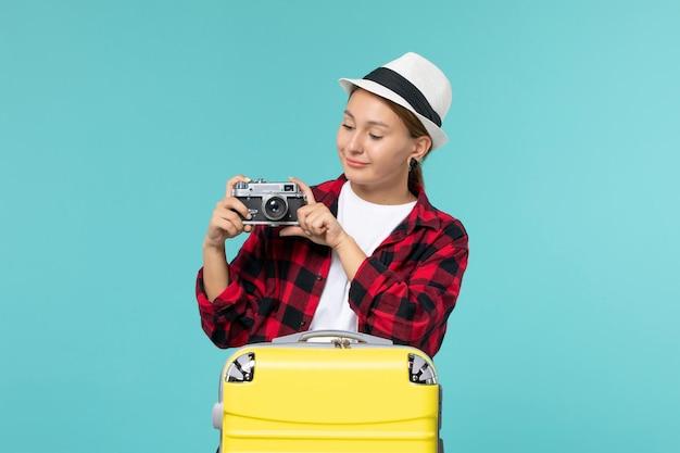 Вид спереди молодая женщина собирается в поездку и держит камеру на синем полу, путешествуя на самолете по морю