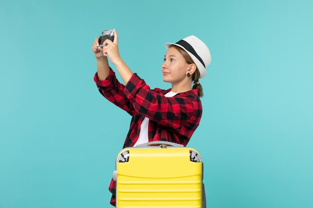 Вид спереди молодая женщина собирается в поездку и держит камеру на голубом пространстве