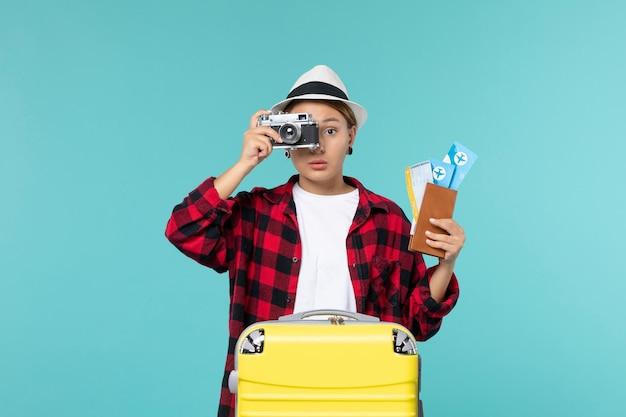 水色の空間でチケットとカメラを持って旅行に行く若い女性の正面図