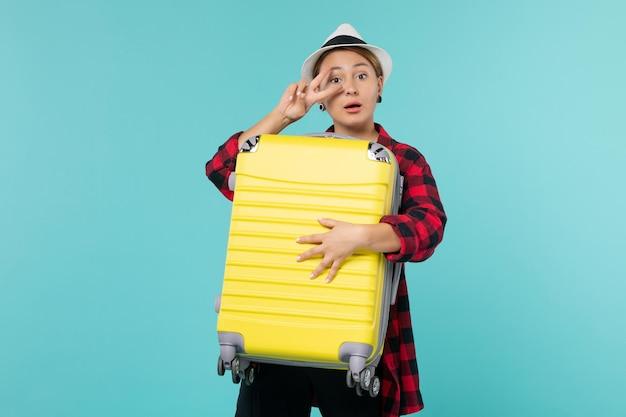 파란색 책상에 그녀의 큰 가방과 함께 휴가에가 전면보기 젊은 여성