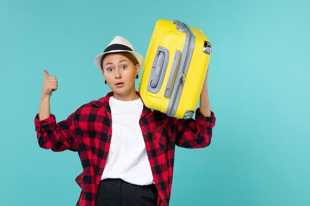 Вид спереди молодая женщина, отправляющаяся в отпуск со своей большой сумкой на синем пространстве