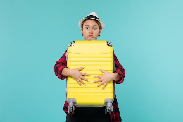 Вид спереди молодая женщина, отправляющаяся в отпуск со своей большой сумкой на голубом пространстве