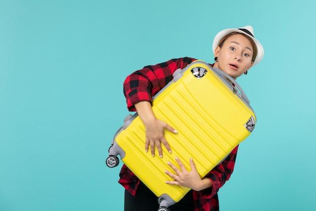 青いスペースに彼女の大きなバッグを持って休暇に行く若い女性の正面図