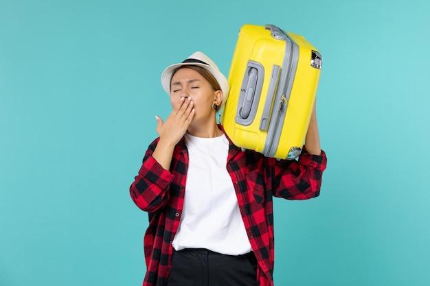 青いスペースであくびをしている彼女の大きなバッグと一緒に休暇に行く正面図若い女性