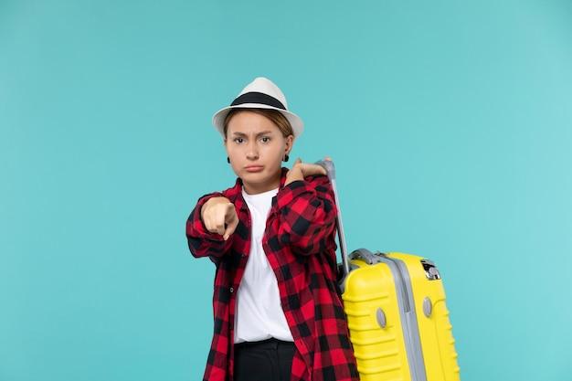 푸른 공간에 그녀의 노란 가방과 함께 휴가를가는 전면보기 젊은 여성