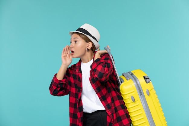 밝은 파란색 공간에 그녀의 노란 가방과 함께 휴가를가는 전면보기 젊은 여성