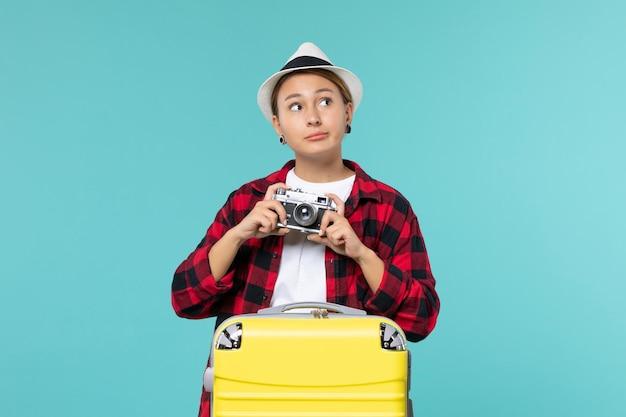 Giovane femmina di vista frontale che va in viaggio e che tiene la macchina fotografica sullo scrittorio blu