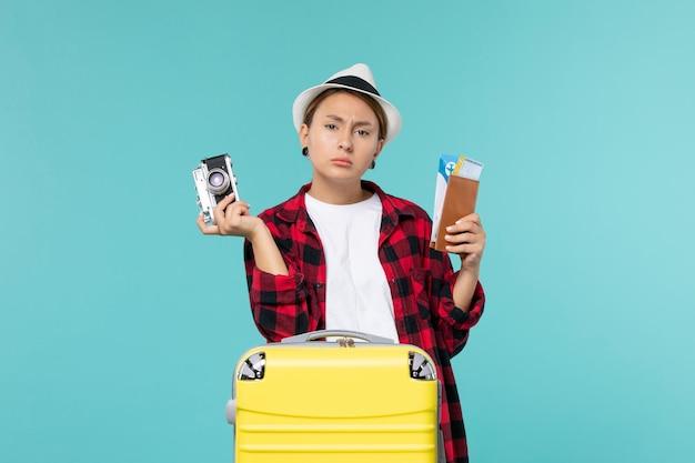 Giovane femmina di vista frontale che va in viaggio che tiene i biglietti e la macchina fotografica sullo spazio blu