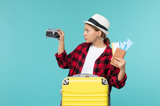 Giovane femmina di vista frontale che va in viaggio che tiene i biglietti e la macchina fotografica sullo spazio azzurro