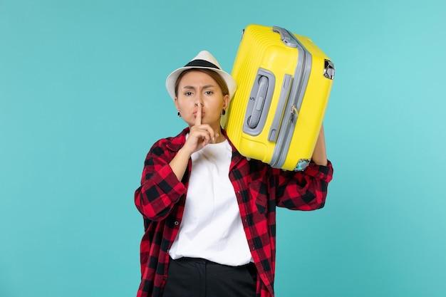 Giovane femmina di vista frontale che va in vacanza con la sua grande borsa sullo spazio blu-chiaro