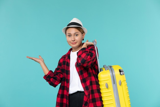Front view young female going in vacation with her yellow bag on blue desk