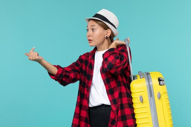 Giovane femmina di vista frontale che va in vacanza con la sua borsa gialla sullo spazio blu