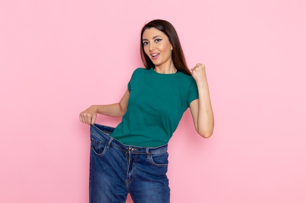 Front view young female in green t-shirt checking her waist on light-pink wall waist sport exercise workouts beauty slim athlete female