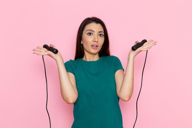 Giovane femmina di vista frontale in maglietta verde che tiene la corda per saltare sullo sport femminile sottile di bellezza di allenamento di esercizio della vita della parete rosa