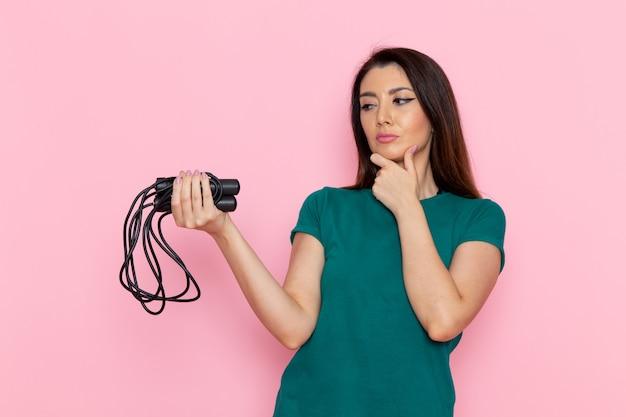 Giovane donna di vista frontale in maglietta verde che tiene la corda per saltare e pensare sul muro rosa chiaro esercizio allenamento bellezza sottile sport femminile