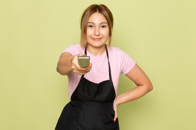 A front view young female hairdresser in pink t-shirt and black cape holding hair machine smiling on green