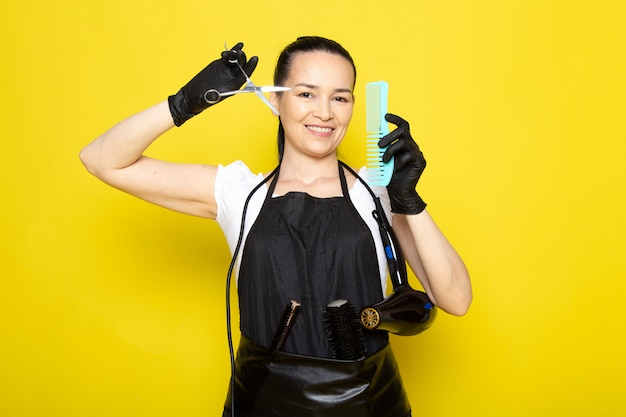 A front view young female hairdresser in white t-shirt black cape in black gloves holding scissors and brush smiling