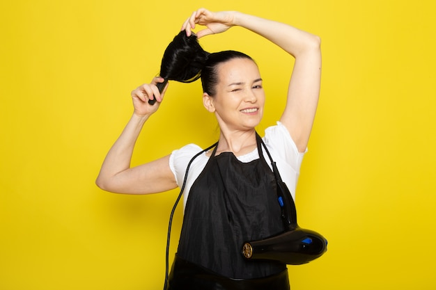 A front view young female hairdresser in white t-shirt black cape brushing her hair smiling posing
