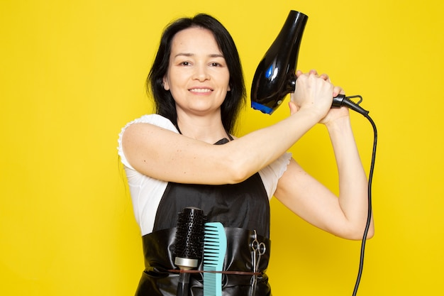 A front view young female hairdresser in white t-shirt black cape holding black hairdryer smiling