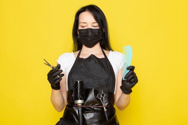 A front view young female hairdresser in white t-shirt black cape holding blue hairbrush and scissors in black sterile mask black gloves