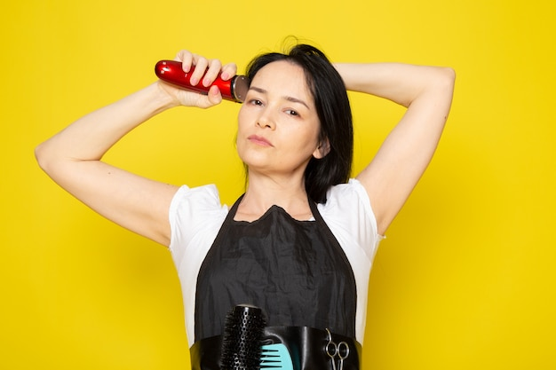 A front view young female hairdresser in white t-shirt black cape using mechanical hair machine wave hair