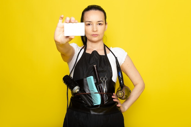 A front view young female hairdresser in white t-shirt black cape with brushes and hairdryer holding white card posing