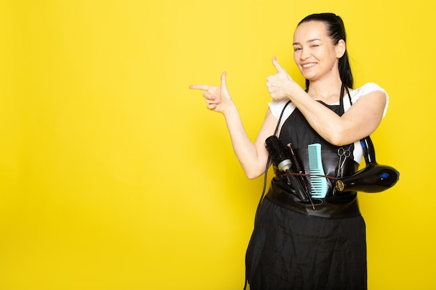 A front view young female hairdresser in white t-shirt black cape with brushes and hairdryer smiling welcoming posing