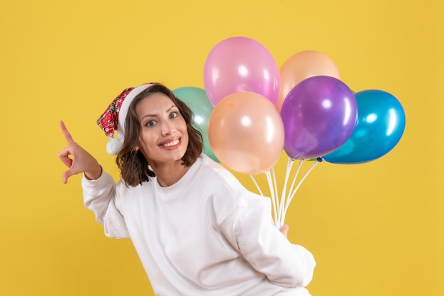 Front view young female happily hiding colorful balloons on a yellow background new year christmas color holiday woman emotions