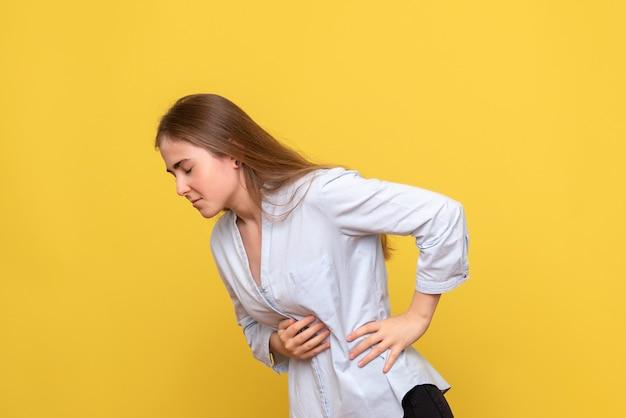 Vista frontale della giovane donna che ha mal di stomaco