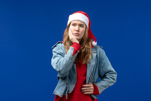 Вид спереди молодой женщины с зубной болью на синем фоне цвета рождественских эмоций