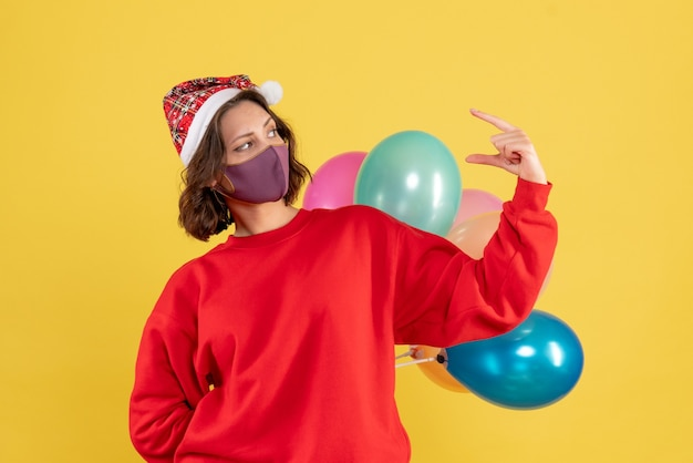 Front view young female hiding balloons in sterile mask christmas woman holiday color emotion new year