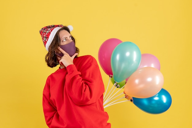 Front view young female hiding balloons in sterile mask christmas woman holidays color emotion new year