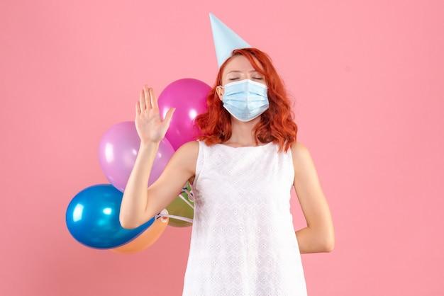 正面図ピンクの背景パーティーcovid-クリスマス新年の色の滅菌マスクで彼女の背中の後ろにカラフルな風船を隠している若い女性