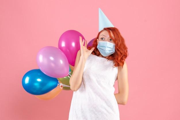 ピンクのデスクパーティーcovid-クリスマス新年の色の滅菌マスクで彼女の背中の後ろにカラフルな風船を隠している正面図若い女性