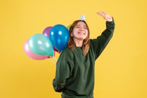 彼女の後ろにカラフルな風船を隠している正面図若い女性