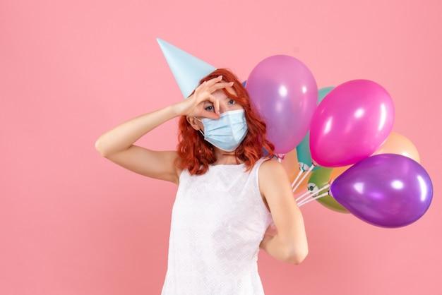 Вид спереди молодая женщина, скрывающая разноцветные воздушные шары в стерильной маске на розовом столе, вечеринка covid - новогодний рождественский цвет