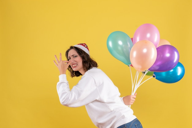 Front view young female hiding colorful balloons on a yellow background new year christmas color holiday woman emotion