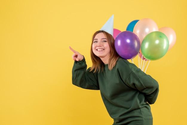 カラフルな風船を隠している正面図若い女性
