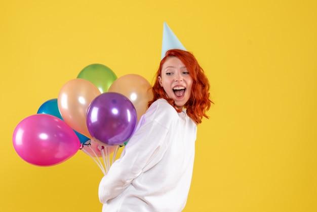 Вид спереди молодая женщина, скрывающая милые разноцветные воздушные шары на желтом