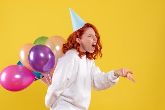 Vista frontale giovane femmina nascondendo simpatici palloncini colorati su uno sfondo giallo festa capodanno colore donna emozione