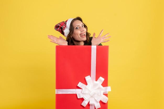 黄色のボックスの中に隠れている正面図若い女性
