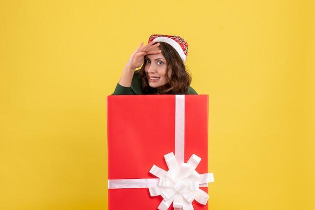 Вид спереди молодая женщина прячется внутри коробки на желтом