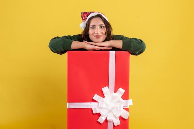 黄色のプレゼントボックスの中に隠れている正面図若い女性