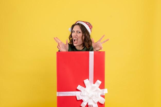 Вид спереди молодая женщина прячется в подарочной коробке на желтом