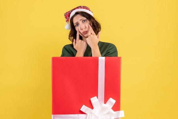 黄色の悲しい顔でプレゼントボックスの中に隠れている正面図若い女性