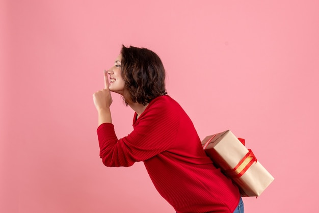 Front view young female hiding xmas present behind her back on pink desk christmas holiday emotion woman new year