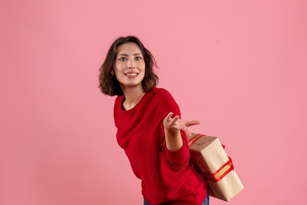 Front view young female hiding xmas present behind her back on a pink
