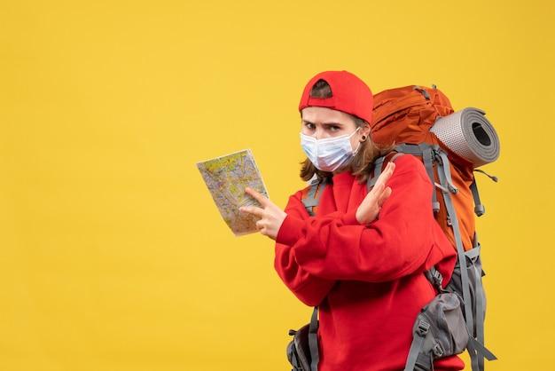 正面図の若い女性のハイカー、バックパックとマスクを持って地図交差点