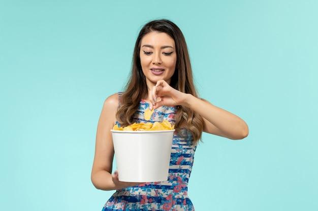 正面図青い表面にチップを持って食べている若い女性
