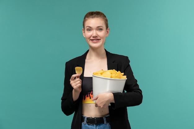 Вид спереди молодая женщина, держащая и едящая чипсы, смотрит фильм на синем столе
